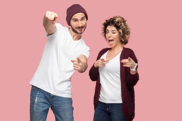Портрет забавной удивленной пары друзей в непринужденной обстановке, стоящей и указывающей на вас фигрера, смотрящей в камеру и подмигивающей. изолированный, закрытый, студийный снимок, розовый фон