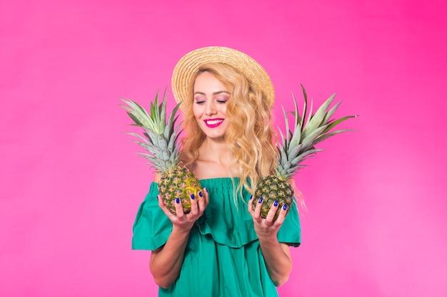 재미있는 여자와 분홍색 벽에 파인애플의 초상화. 여름, 다이어트 및 건강한 라이프 스타일 개념.
