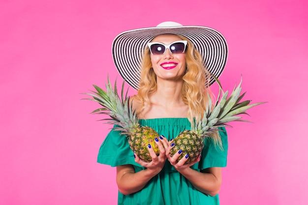 ピンクの壁の上の面白い女性とパイナップルの肖像画。夏、ダイエット、健康的なライフスタイルのコンセプト。