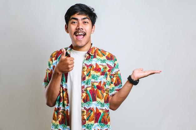 コピースペースと赤い背景に対して、笑顔で彼の側に何かを提示することを指している白いtシャツの面白い若いアジア人の肖像画