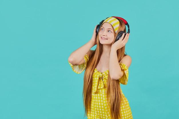 파란색 벽에 고립 된 노란색 드레스에 재미있는 젊은 금발 여자의 초상화. 소녀 음악 스트리밍 서비스를 사용하여 무선 헤드폰으로 음악을 듣습니다.