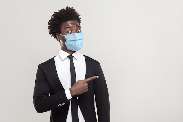 Портрет смешного молодого красивого рабочего человека в черном костюме с хирургической медицинской маской стоя показывая и указывая на пустой фон copyspace. крытая студия выстрел, изолированные на сером фоне.