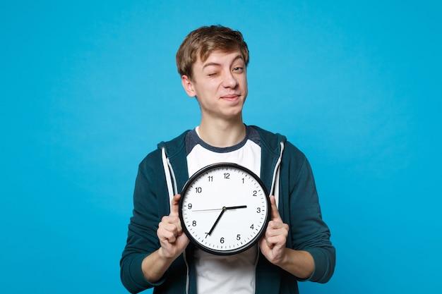 Портрет забавного молодого человека в повседневной одежде мигает, держа круглые часы, изолированные на синей стене. время уходит. люди искренние эмоции, концепция образа жизни.