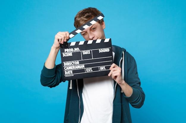 Портрет забавного молодого человека в повседневной одежде, держащего с хлопушкой классического черного фильма, изолированного на синей стене. концепция образа жизни искренние эмоции людей.
