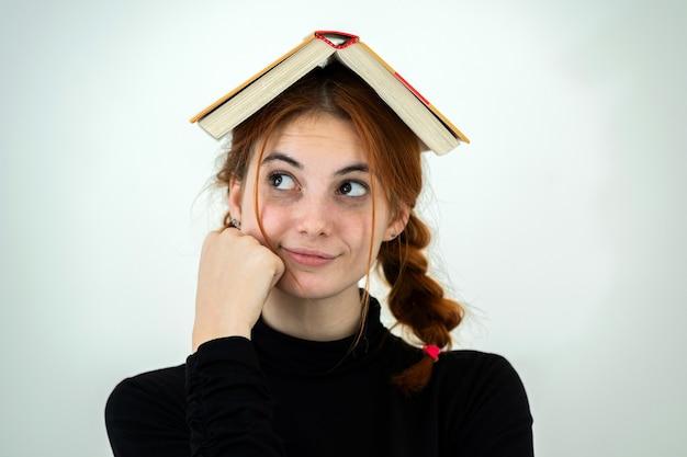 彼女の頭に開いた本を持つ面白い若い笑顔の学生の女の子の肖像画。読書と教育の概念。