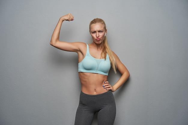 Портрет забавной молодой спортивной блондинки, поднимающей руку и демонстрирующей свою силу, нахмуренных бровями и надутых губ, позирующей на сером фоне, одетой в спортивную одежду