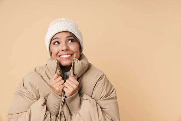 Портрет забавной молодой женщины в зимнем пальто, глядя в сторону и улыбаясь