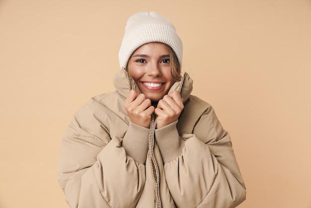 Портрет смешной молодой женщины в зимнем пальто, глядя в камеру и улыбаясь