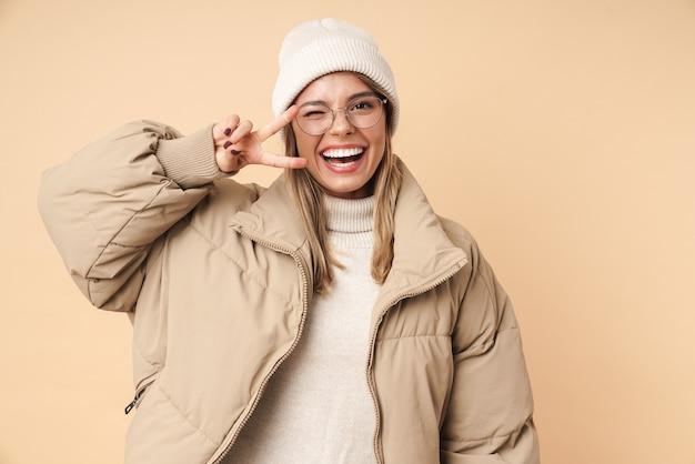 Портрет смешной молодой женщины в зимнем пальто, подмигивая и жестикулируя знак мира