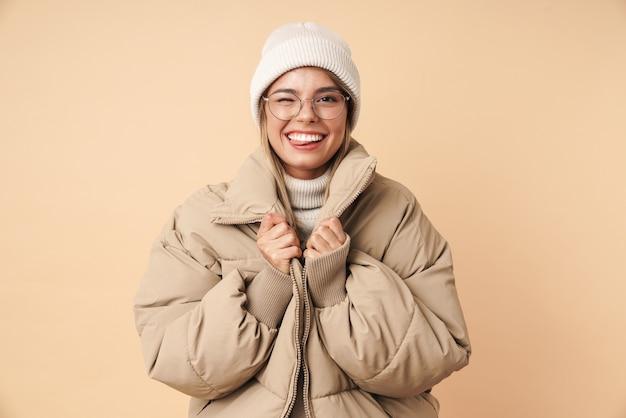 Портрет смешной молодой женщины в зимнем пальто, подмигивая и улыбаясь