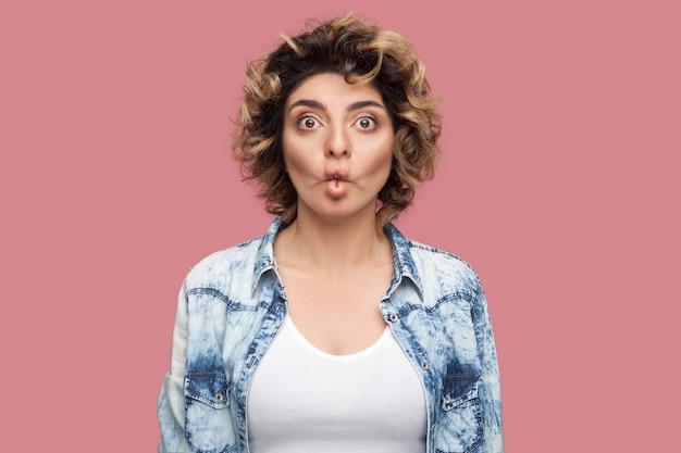 캐주얼한 파란색 셔츠에 곱슬머리를 한 재미있는 젊은 여성의 초상화는 물고기 입으로 서 있고 큰 눈으로 카메라를 보고 있습니다. 실내 스튜디오 촬영, 분홍색 배경에 격리.