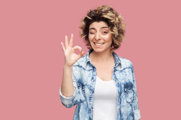 캐주얼 파란색 셔츠에 곱슬머리 헤어스타일을 한 재미있는 젊은 여성의 초상화는 ok 사인 제스처 손, 윙크, 이빨 미소와 카메라를 보고 서 있습니다. 분홍색 배경에 고립 된 실내 스튜디오 촬영