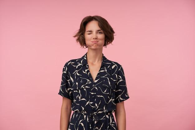 Портрет забавной молодой женщины с короткими каштановыми волосами, надувающей щеки и подмигивающей, находящейся в приподнятом настроении, стоя с опущенными руками
