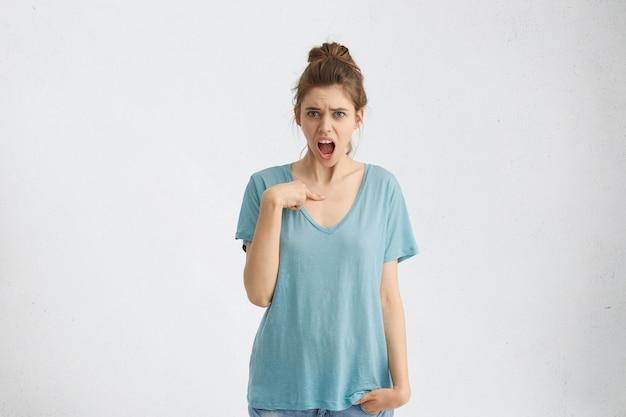 喧嘩しながら非常に感情的である指で自分を指して、青い目と髪の結び目を持つ猛烈な女性の肖像画。一人で仕事をしなければならないことに不満を抱いている怒っている女性