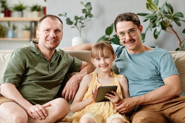 Портрет семьи геев, сидящих на диване с приемной дочерью с помощью цифрового планшета дома