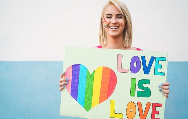 Портрет гей-женщины, держащей знамя любви - это любовь на параде лгбт-прайда - сосредоточьтесь на лице