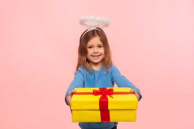 Портрет щедрой доброй ангельской маленькой девочки с нимбом, дающей большой подарок на день рождения камере и улыбающейся, поздравляющей с праздником, делясь подарком. закрытый студийный снимок изолирован на розовом фоне
