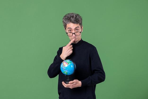 Портрет гения человек держит земной шар студия выстрел зеленый фон планета воздух море учитель космос