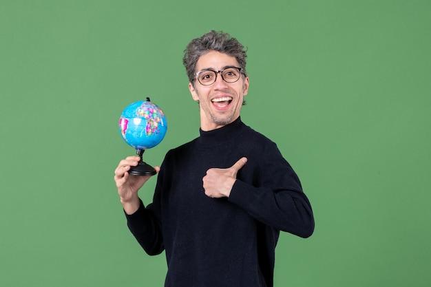 地球儀スタジオショット緑の背景学校空海宇宙教師自然惑星を保持している天才男の肖像