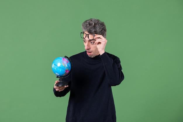小さな地球儀スタジオショット緑の背景自然空間惑星を保持している天才男の肖像