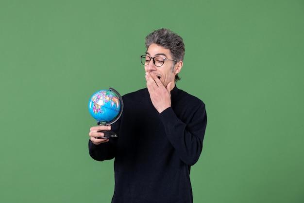 小さな地球儀スタジオショット緑の背景教師自然宇宙惑星を保持している天才男の肖像
