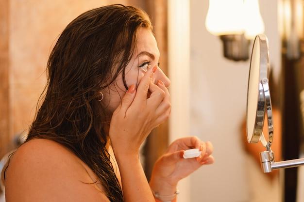 浴室で目のレンズを適用する女の子の肖像画