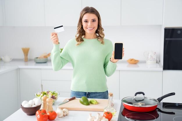Портрет девушки, готовящей домашнюю еду, держа в руках телефонную банковскую карту