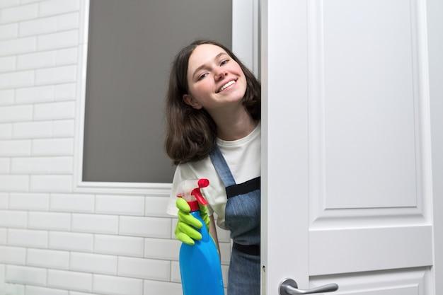 Портрет девушки делают уборку в ванной комнате. подросток в перчатках фартука с моющим средством и тряпичной губкой улыбается, глядя на камеру. уборка, чистота в доме, сервис, концепция молодых людей