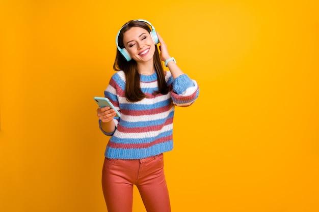 이어폰에서 듣는 음악을 즐기는 여자의 초상화는 전화를 잡아