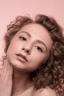 ピンクで隔離の肖像画の女の子の腕を組んで