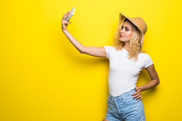 黄色の壁に隔離されたselfieを撮影手にスマートフォンを持っている恋人とビデオ通話を持っている女の子の肖像画。週末の休暇を楽しんでいます