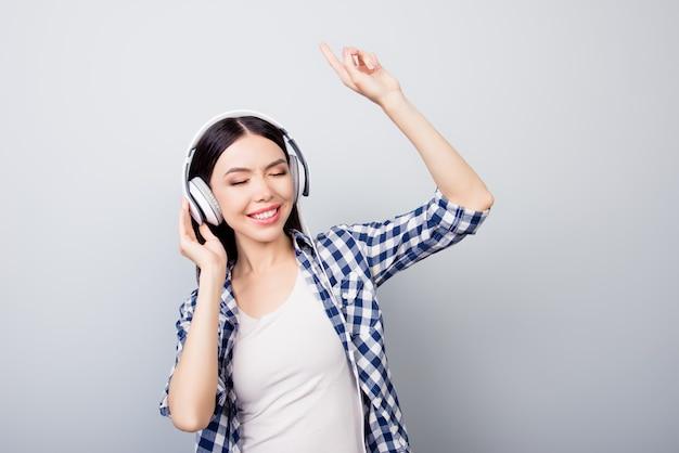 Портрет девушки в повседневной одежде слушает музыку, танцует