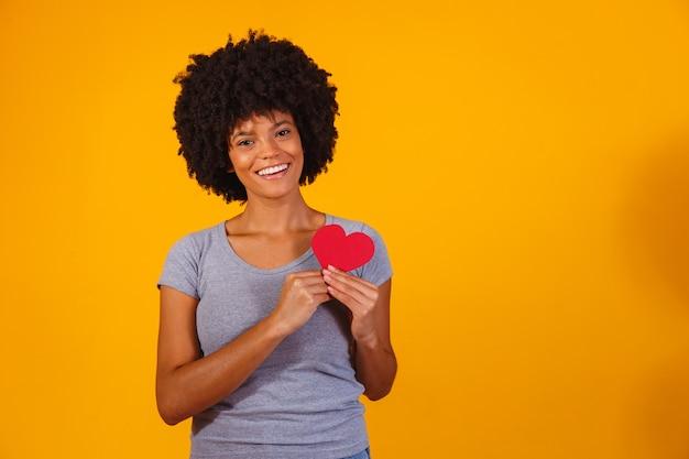 Портрет изолированной девушки с бумажным сердцем на желтом