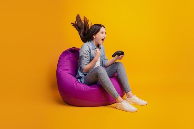 소녀의 초상화는 비디오 게임을 하는 동안 조이스틱을 손에 들고 노란색 벽에 빈백을 앉힙니다.