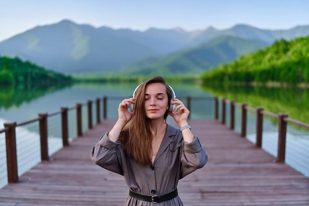 湖と山々の景色を望む桟橋に一人で立って、穏やかで静かな平和な雰囲気を楽しんでいるヘッドフォンで穏やかな音楽を聴いている女の子の肖像画
