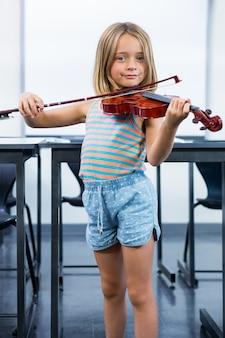 教室でバイオリンを弾く少女の肖像画