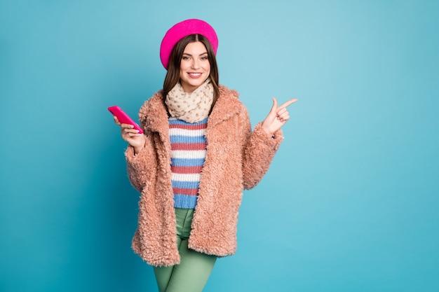 Портрет девушки, указывая копией пространства держать телефон