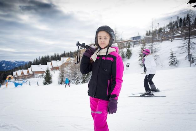 Портрет девушки, позирующей на вершине горнолыжного склона с лыжным снаряжением
