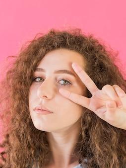 Портрет девушки, показываю знак мира