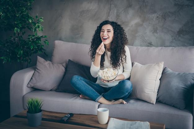 Портрет девушки, сидящей на диване и поедающей кукурузу, смотрит забавное видео в современной промышленной комнате в стиле лофт