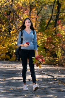 가 공원의 골목을 따라 걷는 여학생의 초상화. 손에 전화와 젊은 아름 다운 여자. 수직 프레임