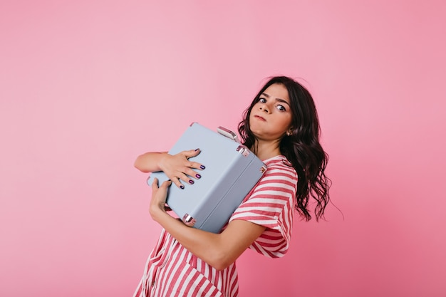 단단히 무거운 서류 가방을 들고 여자의 초상화입니다. 갈색 눈의 여인은 가방의 무게로 몸을 기울였습니다.