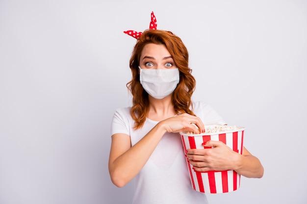 안전 마스크를 쓴 소녀의 초상화 새로운 코미디 사회적 거리를 보고 옥수수를 먹는 영화관을 방문하십시오