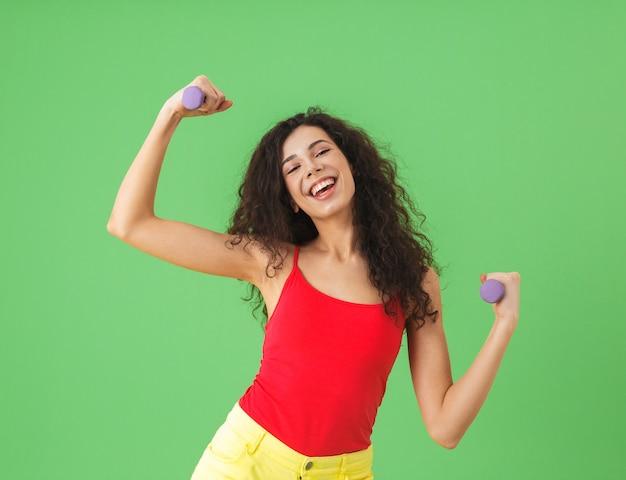Портрет девушки в летней одежде, занимающейся спортом и поднимающей тяжести у зеленой стены