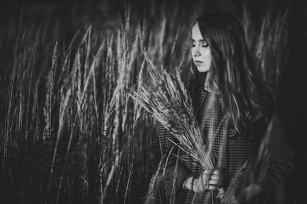 키가 큰 긴 잔디에서 가을에 말린 잔디의 꽃다발을 가진 여자의 초상화