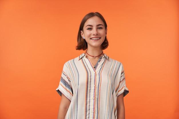 줄무늬 셔츠를 입고 갈색 짧은 머리와 치아 교정기, 코를 뚫은 소녀의 초상화. 오렌지 벽에 카메라를보고 웃는 소녀