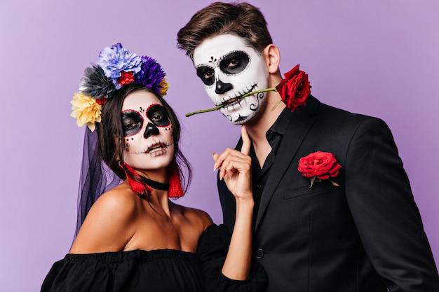 그의 이빨에 장미와 함께 열정적 인 남자의 그려진 된 얼굴을 만지고 검은 머리에 꽃을 가진 여자의 초상화.