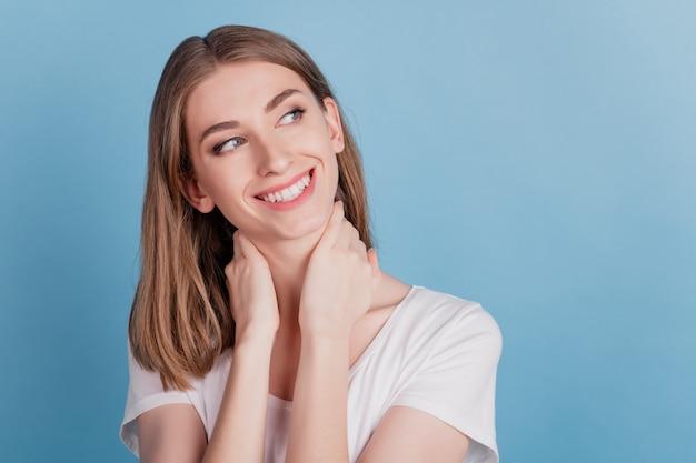 소녀 같은 달콤한 숙녀 손바닥 목의 초상화는 파란색 배경에 빈 공간 이빨 미소를 보입니다