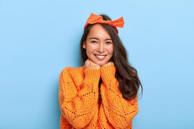 嬉しいブルネットのミレニアル世代の女性の肖像画は、両手をあごの下に保ち、心地よく微笑んで、オレンジ色の弓のヘッドバンド、暖かいオレンジ色のニットセーターを着ています
