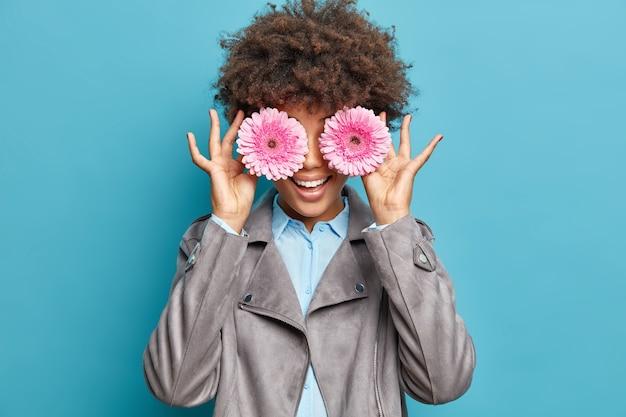 기쁜 곱슬 머리 젊은 여자의 초상화는 두 개의 분홍색 거베라 꽃으로 눈을 덮고 파란색 벽 위에 절연 셔츠와 회색 재킷을 입고 행복하게 봄 분위기 미소가 영감을 찾습니다